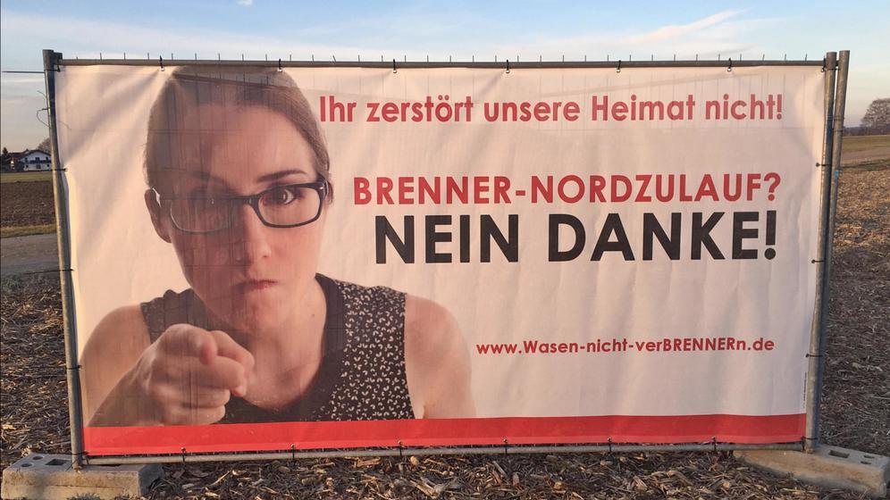 Wie überall im oberbayerischen Inntal stehen oder hängen auch in Rosenheim Protestplakate- und Banner gegen den Brennernordzulauf, hier im Rosenheimer Süden, im Stadtteil Aising. Auch hier könnte die Trasse des Brenner-Nordzulaufs durchgehen. Im Hintergrund rechts die Hochries und links die Kampenwand. | Bild:BR/Martin Binder