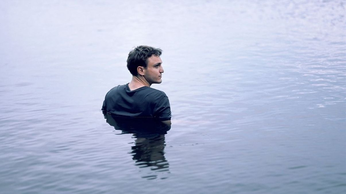 Man sieht den Schauspieler Franz Rogowski bis zum Oberkörper im Wasser eines Sees stehen. Er trägt ein blaues T-Shirt und schaut zur Seite.