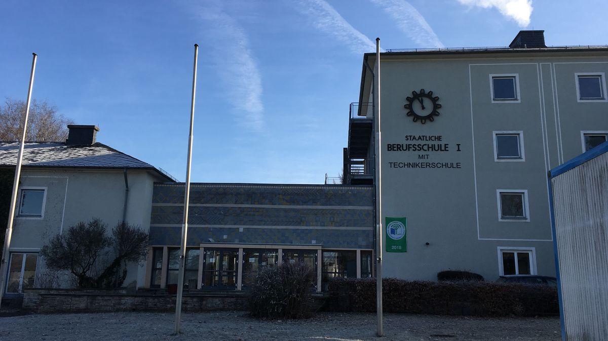 """""""Staatliche Berufsschule I mit Technikerschule"""" steht auf der Fassade der Schule, davor drei Fahnenmasten."""