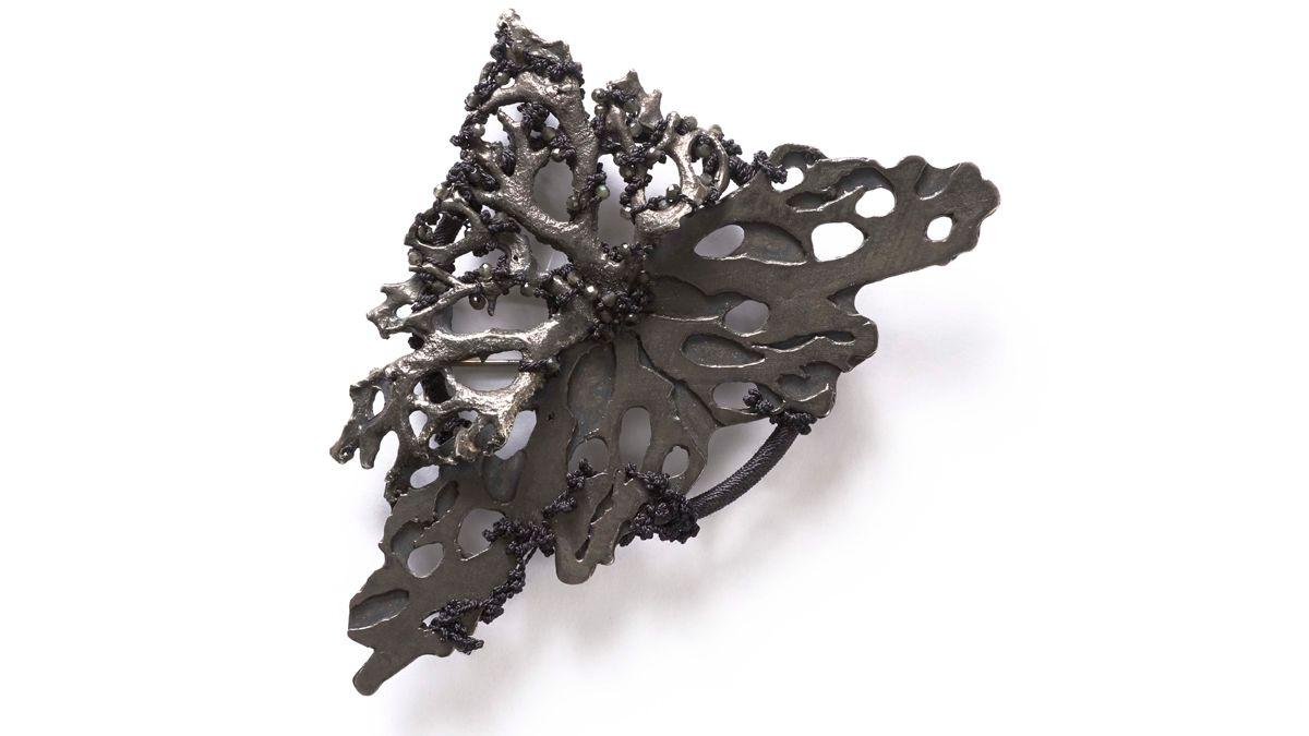 Brosche aus Metall mit geknotetem Faden