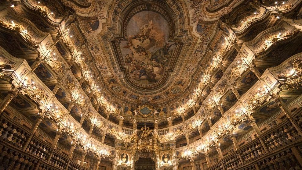 Blick von der Bühne nach oben auf die Zuschauerränge des Opernhauses, die goldverziert und beleuchtet sind.