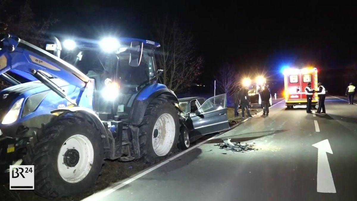 Ein Auto ist auf einen Traktor aufgefahren und im Frontbereich total beschädigt, im Hintergrund ein Feuerwehrauto.