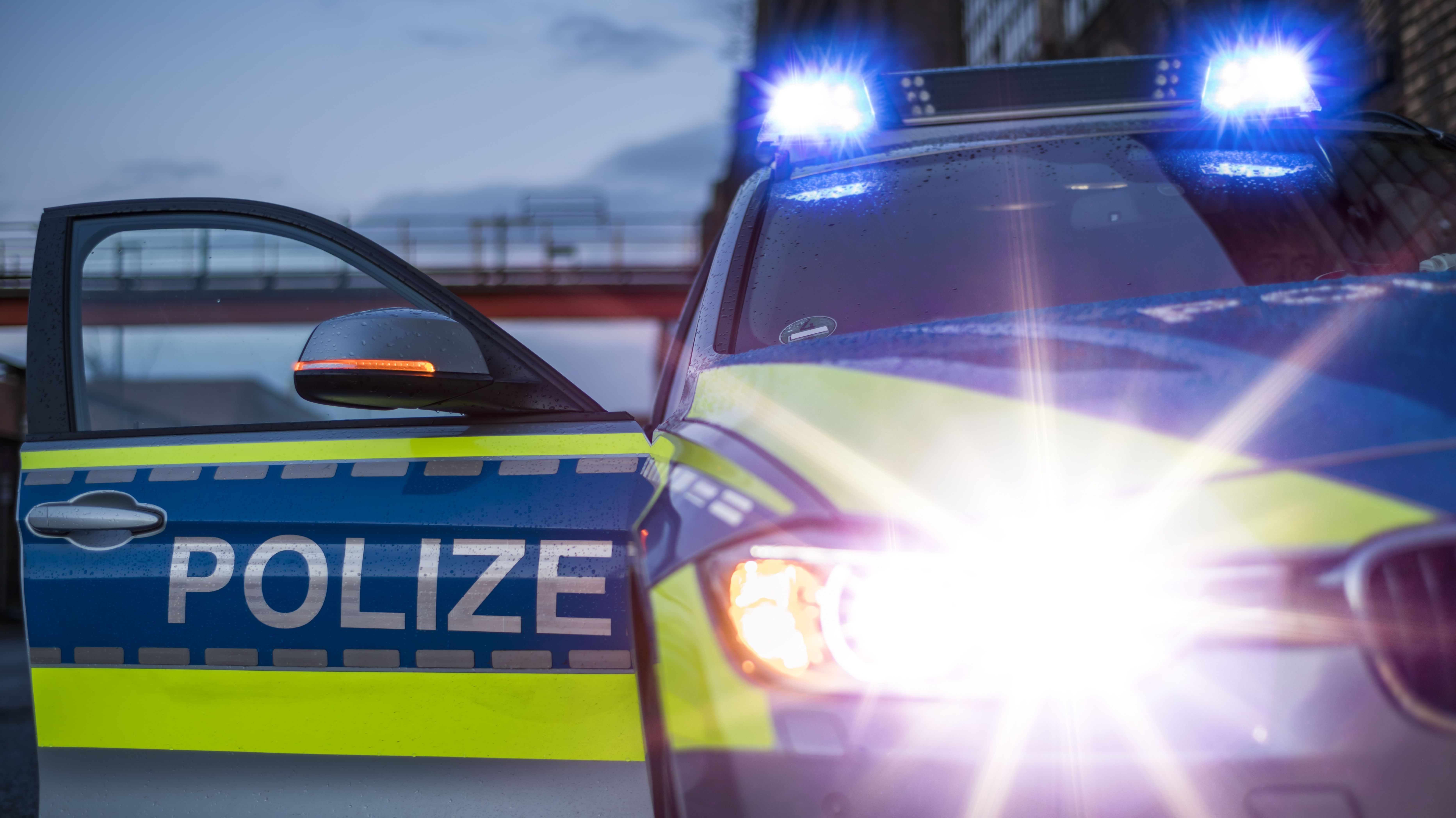Ein Polizeifahrzeug mit Blaulicht in Betrieb und offener Tür