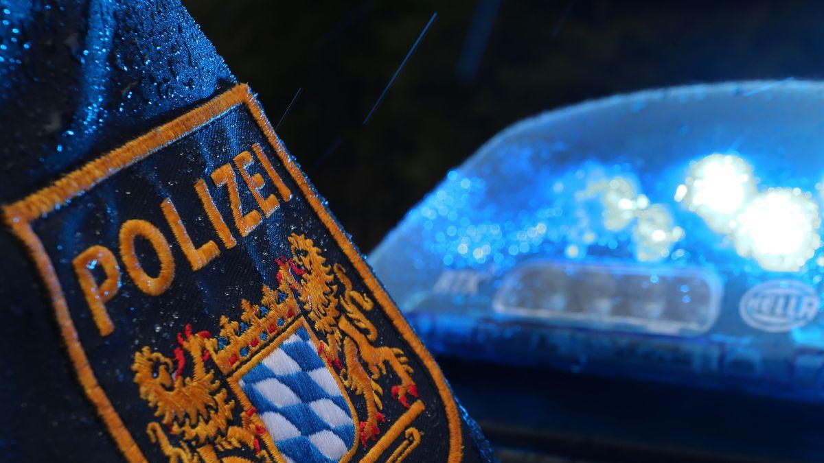 Ein Polizist steht im Regen vor einem Streifenwagen, dessen Blaulicht aktiviert ist.