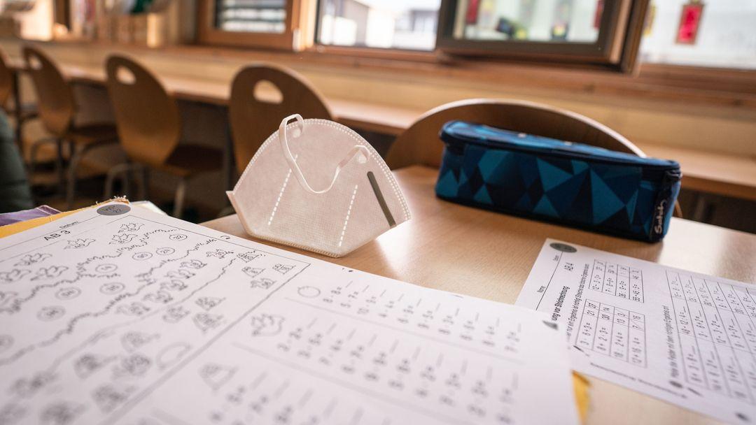 Eine FFP2-Maske liegt in einem Klassenzimmer auf einem Tisch.