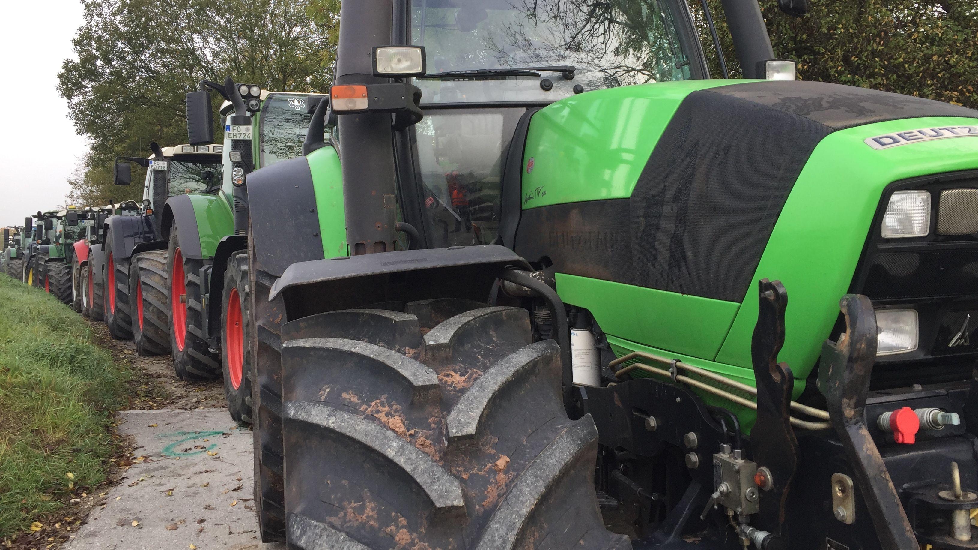 Viele Traktoren stehen in Reih und Glied auf einem Feldweg.