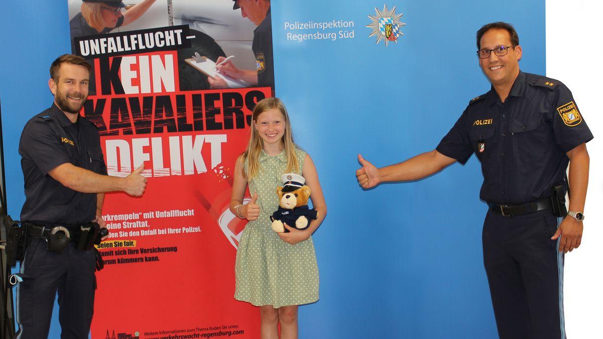 Stefan Pöll und Bernhard Huber überreichen der 10-jährigen Eva einen Polizei-Teddy
