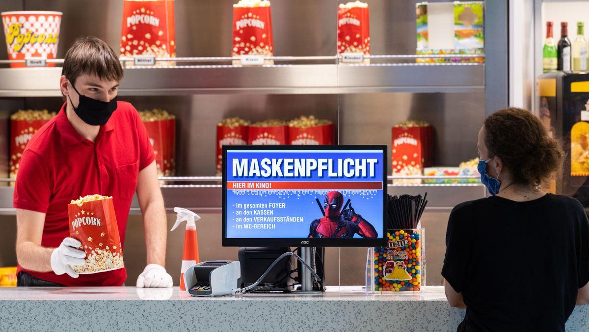 Ein Kinoangestellter verkauft Popcorn mit Maske.