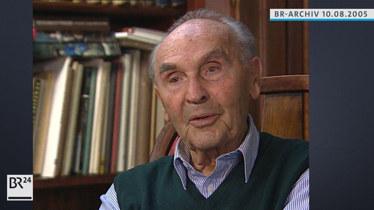 Willy Purucker sitzend vor einem Bücherregal