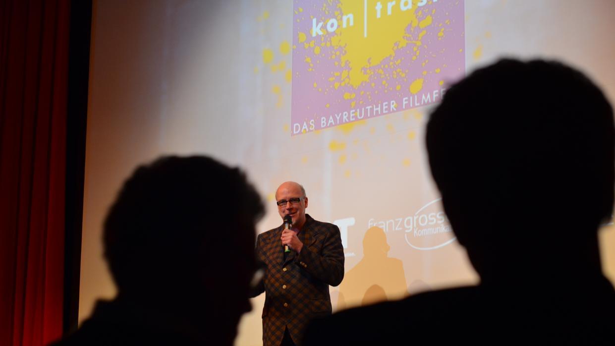 """Ein Moderator steht vor einer Leinwand mit der Aufschrift """"kontrast"""" auf der Bühne"""