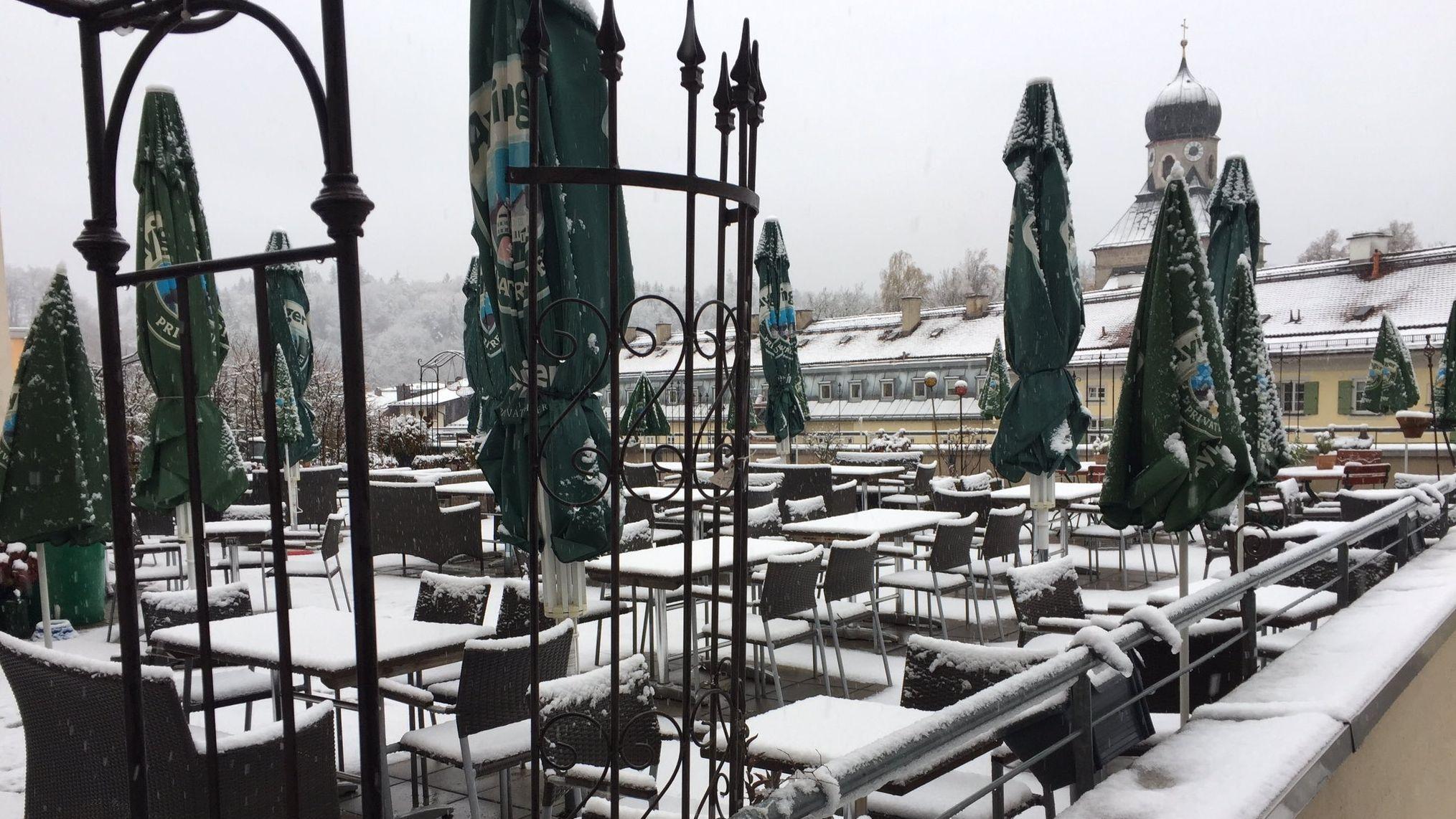 Schneebedeckte Tische und Stühle auf der Terrasse eines Gasthauses in Traunstein