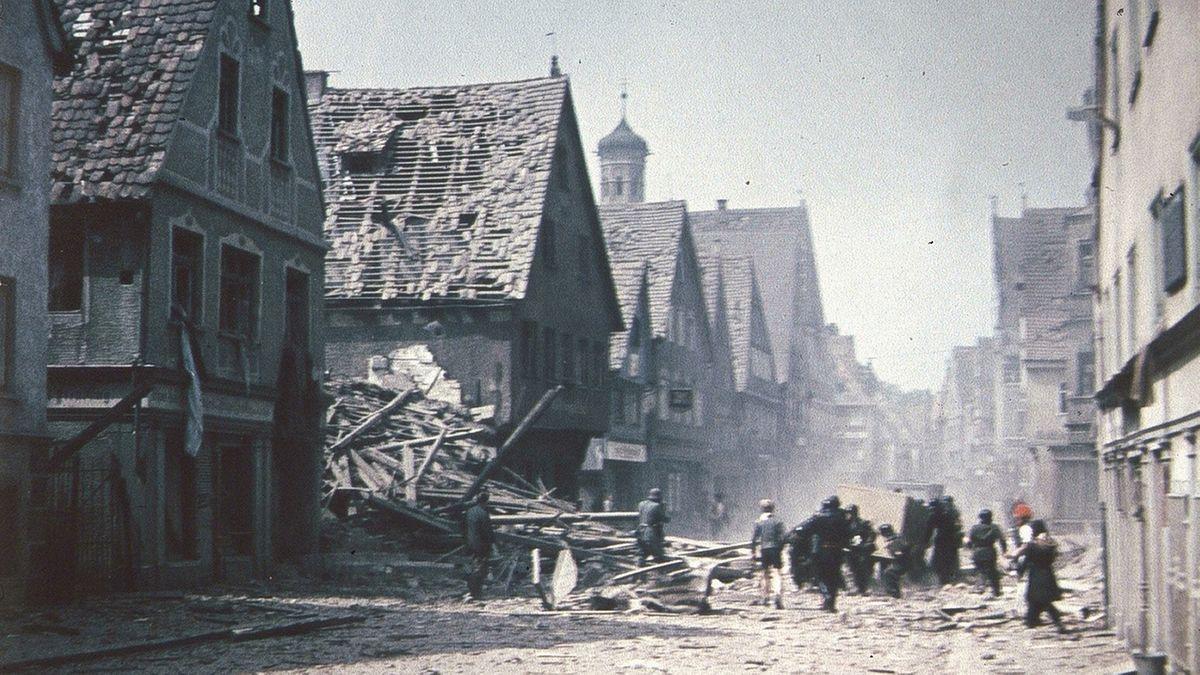 Die Kalchstraße in Memmingen kurz vor Kriegsende voller Schutt, viele Häuser sind stark beschädigt.