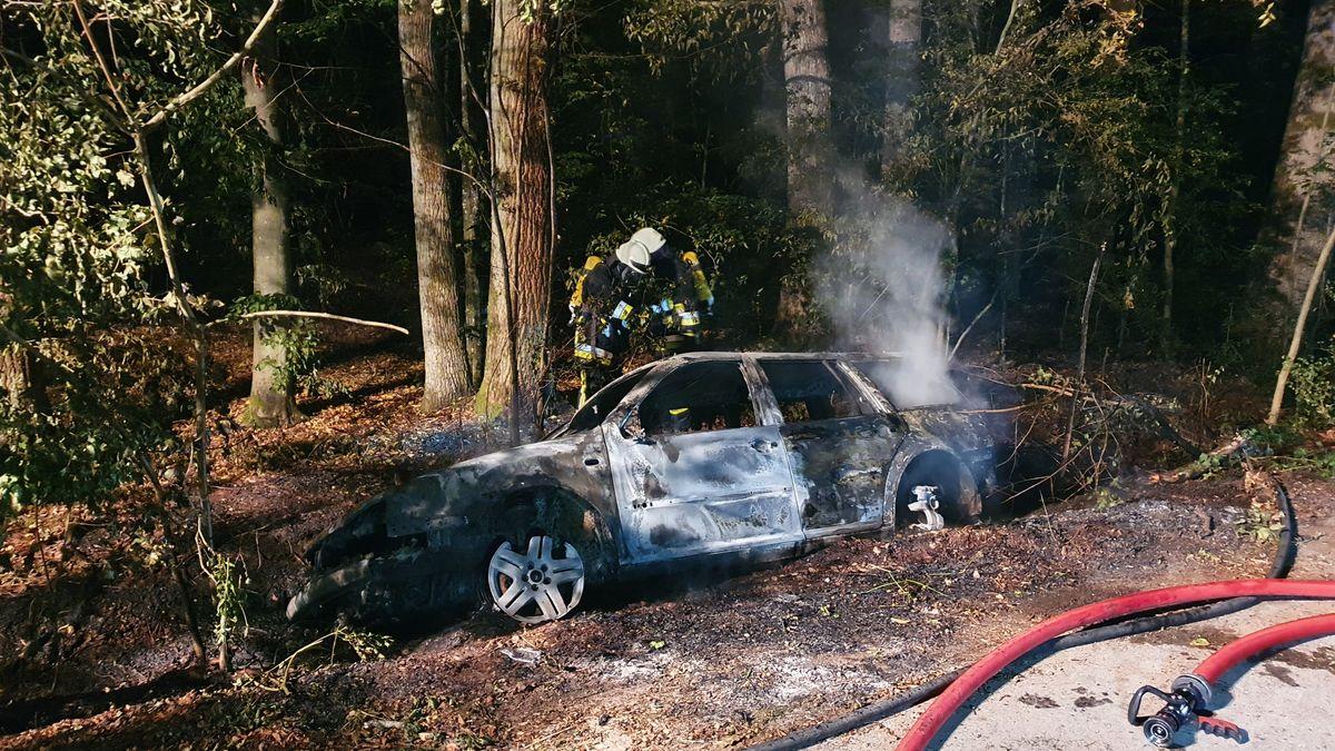Einsatzkräfte der Feuerwehr löschen das komplett ausgebrannte Auto