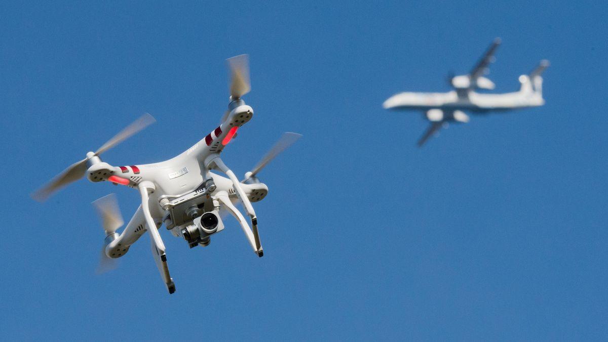 Eine private Drohne fliegt in weiter Entfernung von einem Flugzeug (Symbolbild)