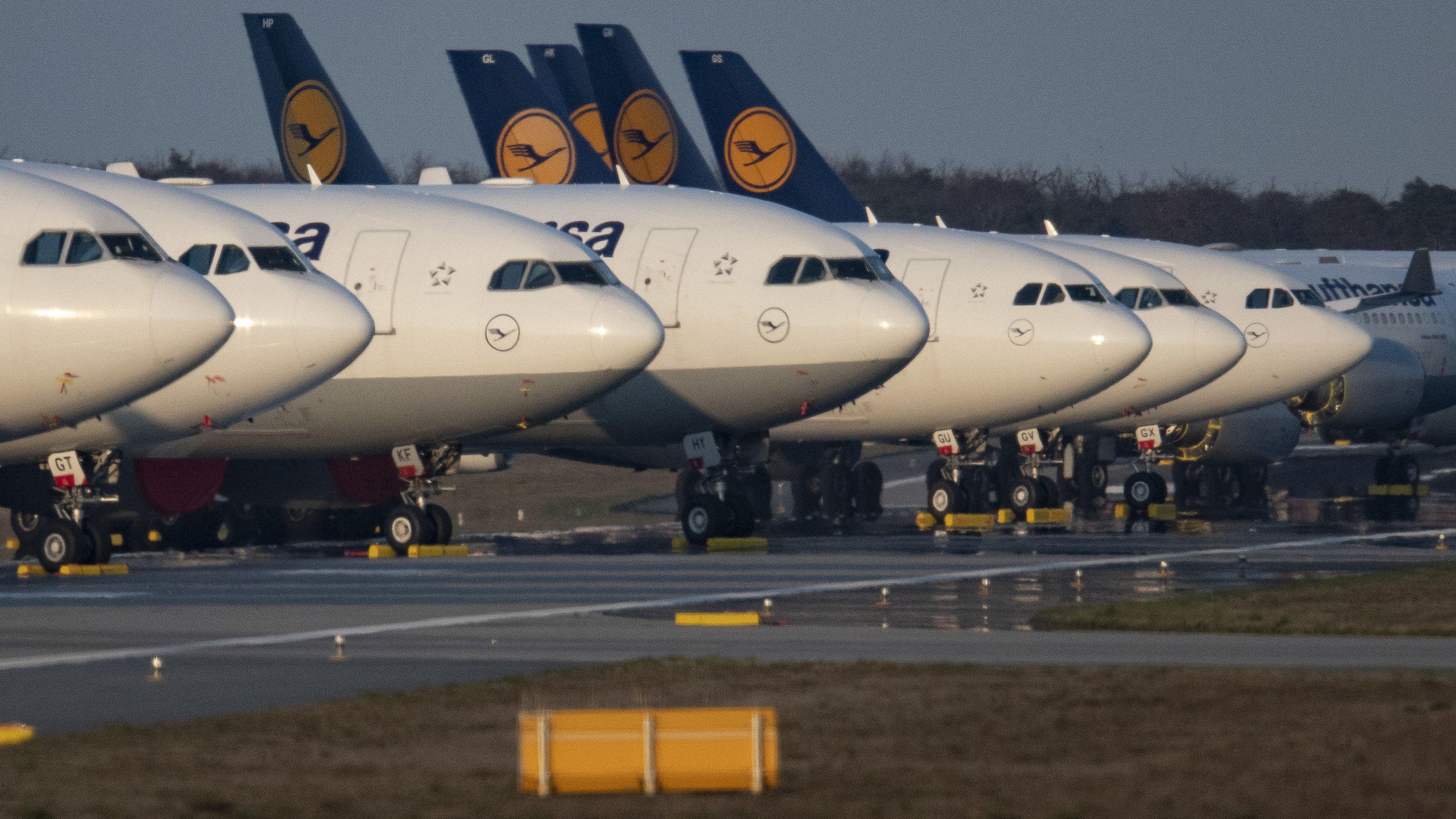 Passagiermaschinen der Lufthansa sind auf einer Landebahn geparkt.