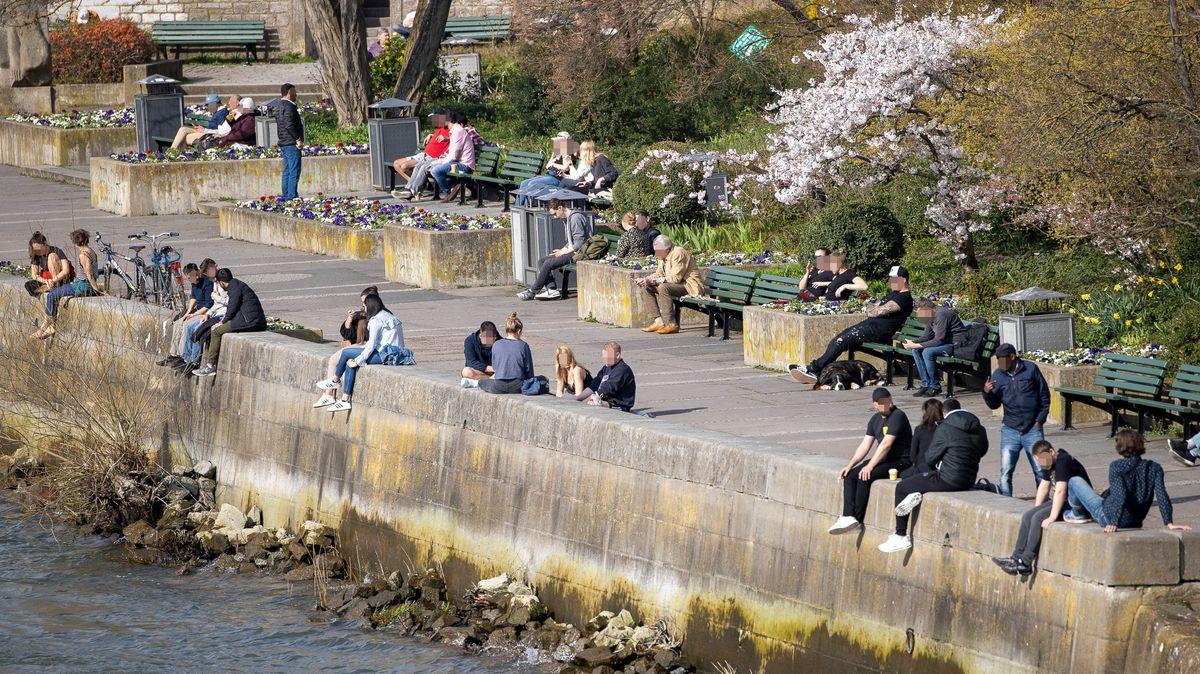 Menschen sitzen in Würzburg am Mainufer.