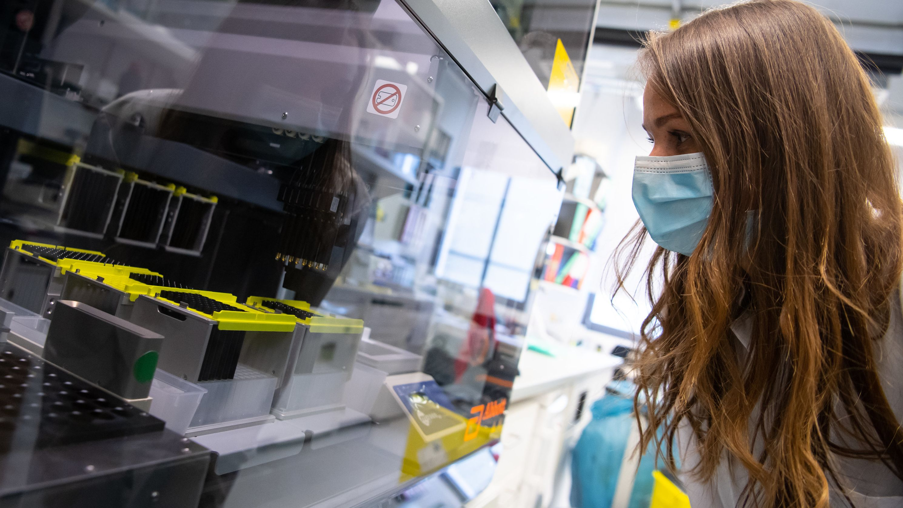 Eine Mitarbeiterin am Institut für Virologie der technischen Universität München (TUM) überprüft einen Pipettierroboter der Proben von Menschen mit Covid-19 Verdacht in einem Labor für die weitere Analyse vorbereitet.