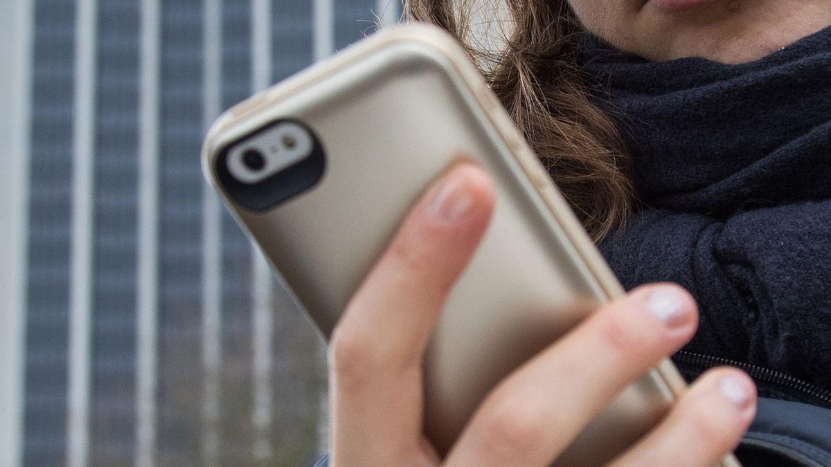 Eine junge Frau schaut irritiert auf ihr Smartphone