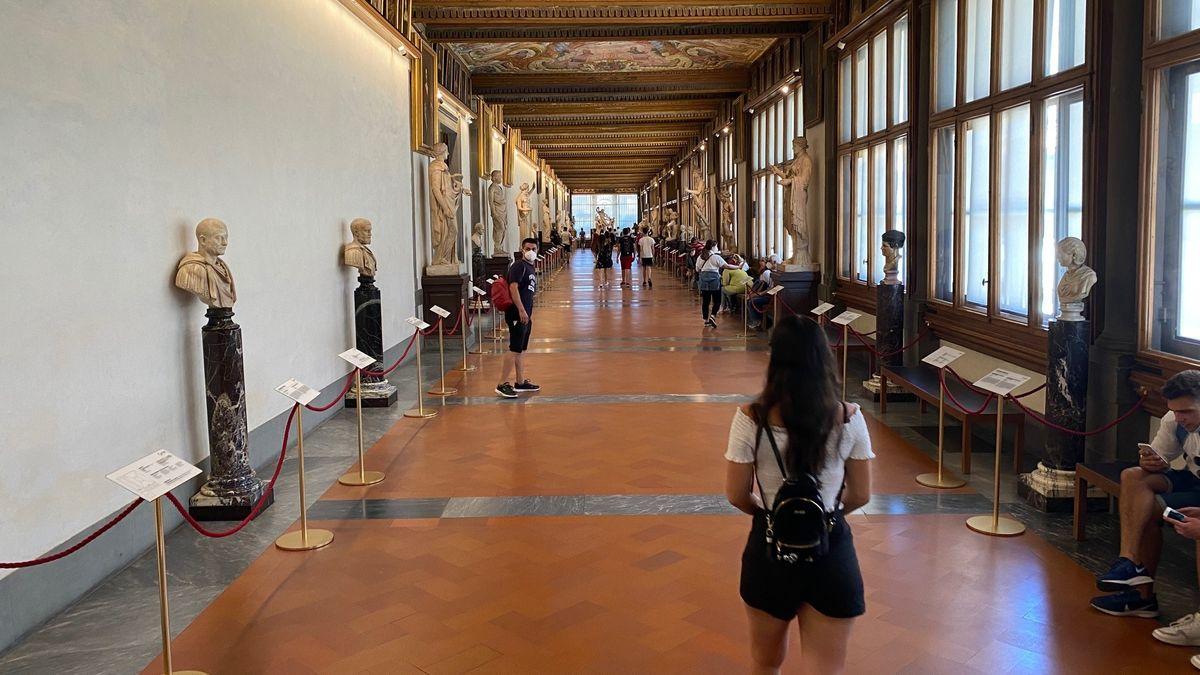 Blick in einen Gang in den Uffizien mit Büsten an den Seiten, eine Besucherin von hinten.