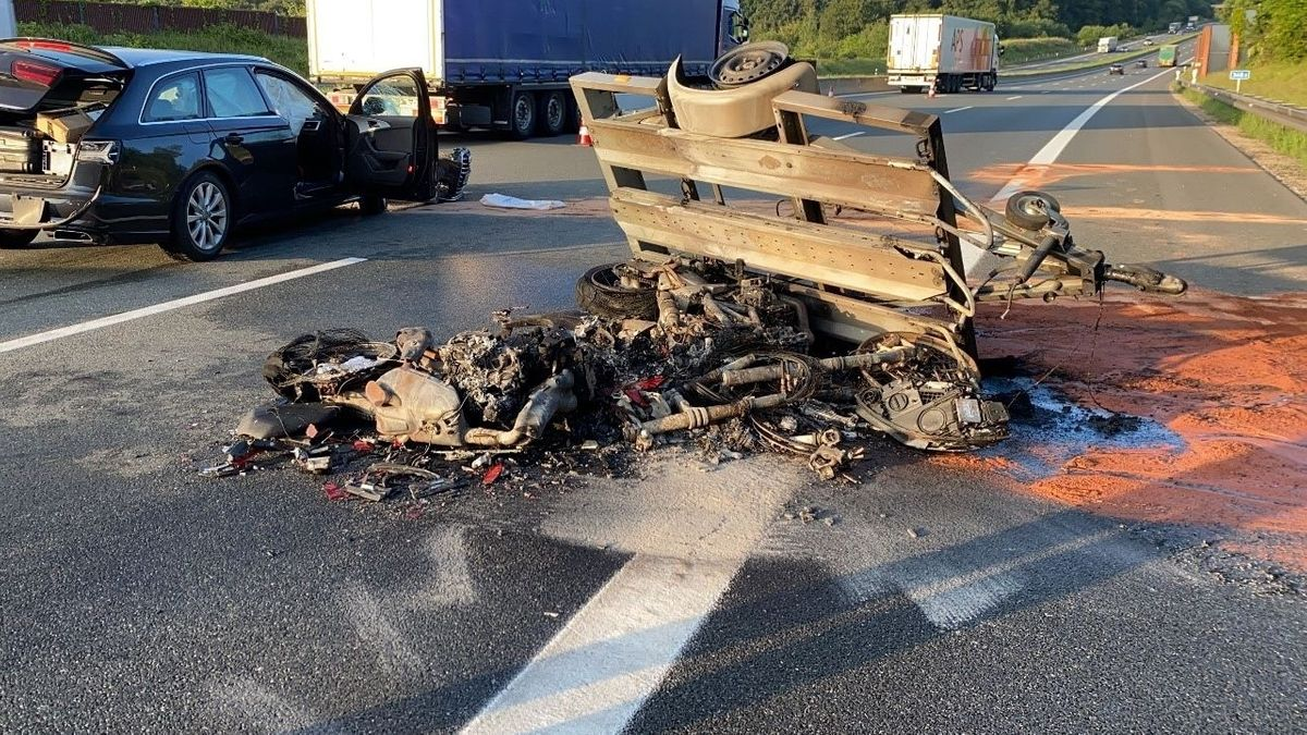Vor dem umgekippten Anhänger liegen die Reste von zwei ausgebrannten Motorrädern.