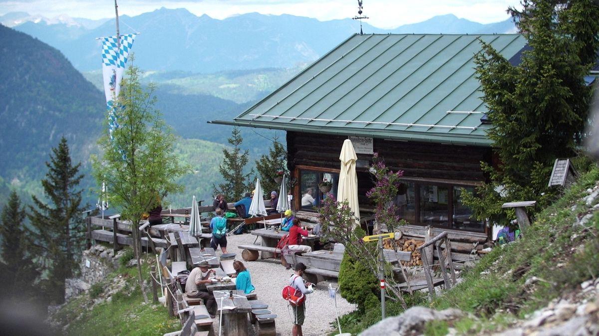 Mit Abstand zueinander sitzende Gäste auf der Terrasse der Berghütte