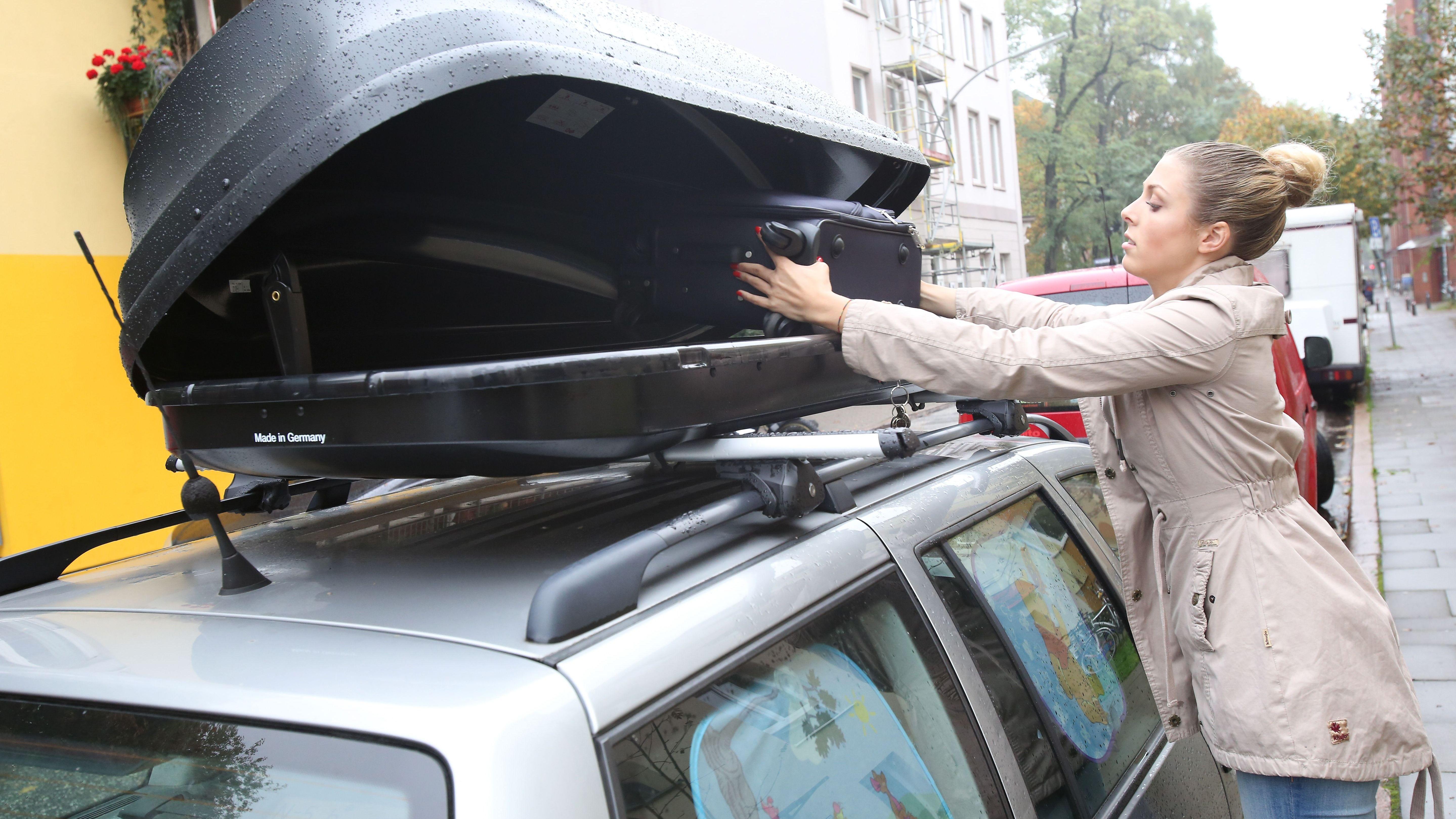 Frau packt einen Koffer in die Dachbox ihres Autos.