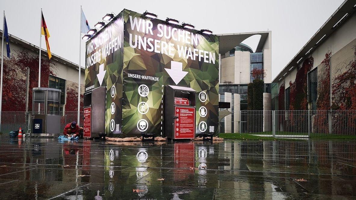 """Großcontainer mit dem Text """"Wir suchen unsere Waffen"""" vor dem Kanzleramt in Berlin"""
