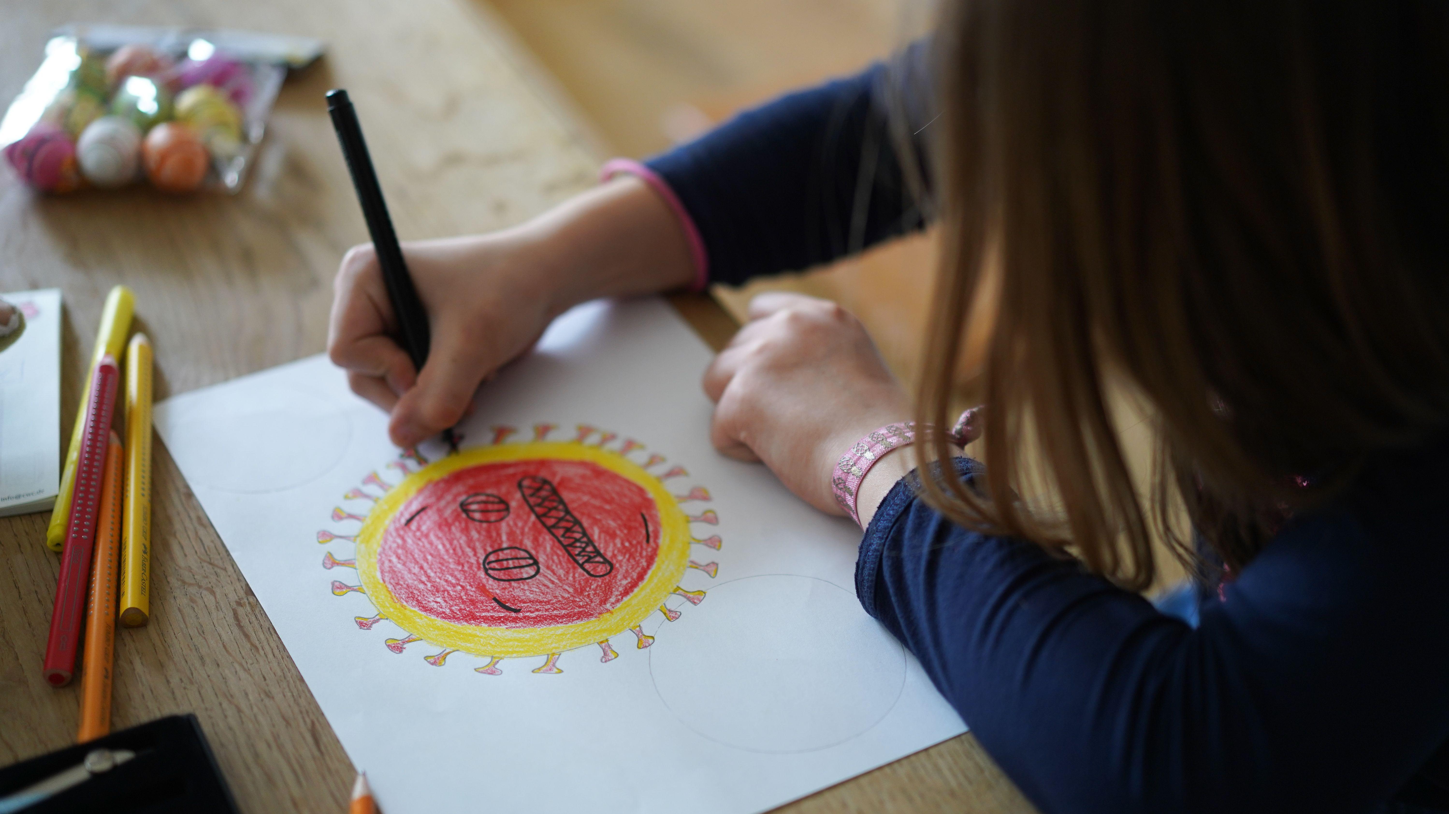 Ein Mädchen versucht, das Coronavirus zu zeichnen (Symbolbild).