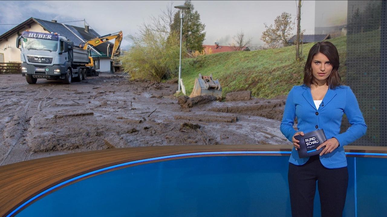 Sandra Rieß vor Bild mit Aufräumungsarbeiten nach Schlammlawine