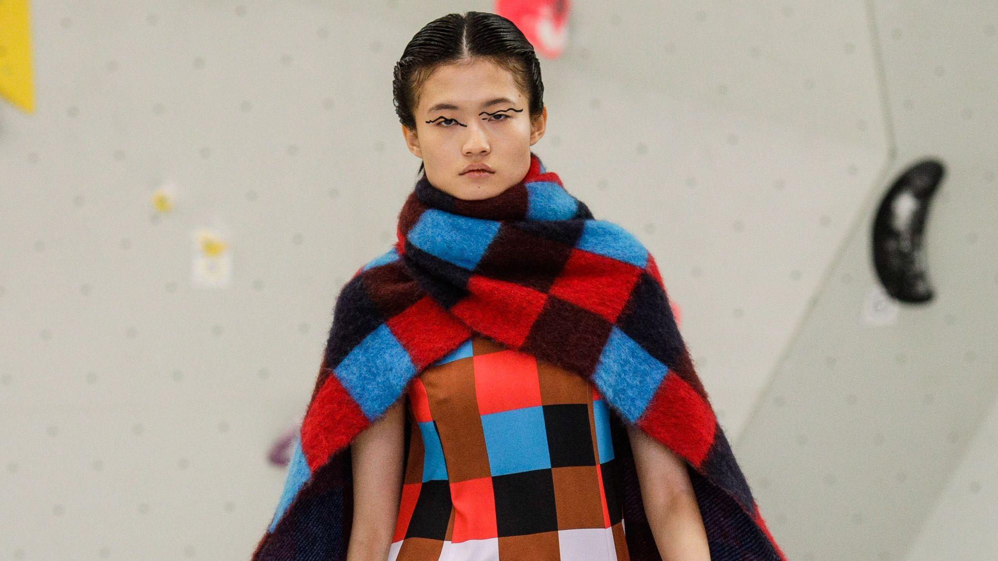 Ein Model trägt ein Kleid und einen groben Schal, beides in buntem Karomuster.