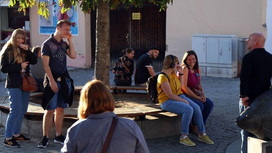 Junge Leute mit Kopfhörern und Handy-Kopfhörern sitzen auf einer Bank unter einem Baum.