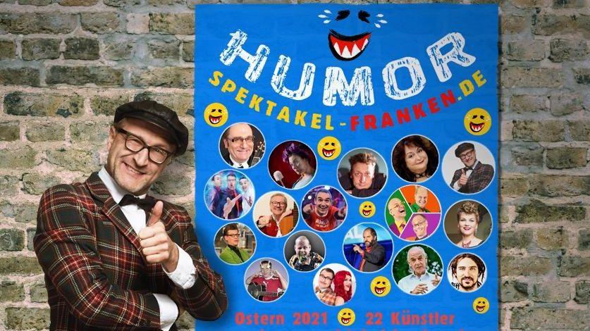 """Oliver Tissot vor dem Plakat """"Humorspektakel Franken"""""""