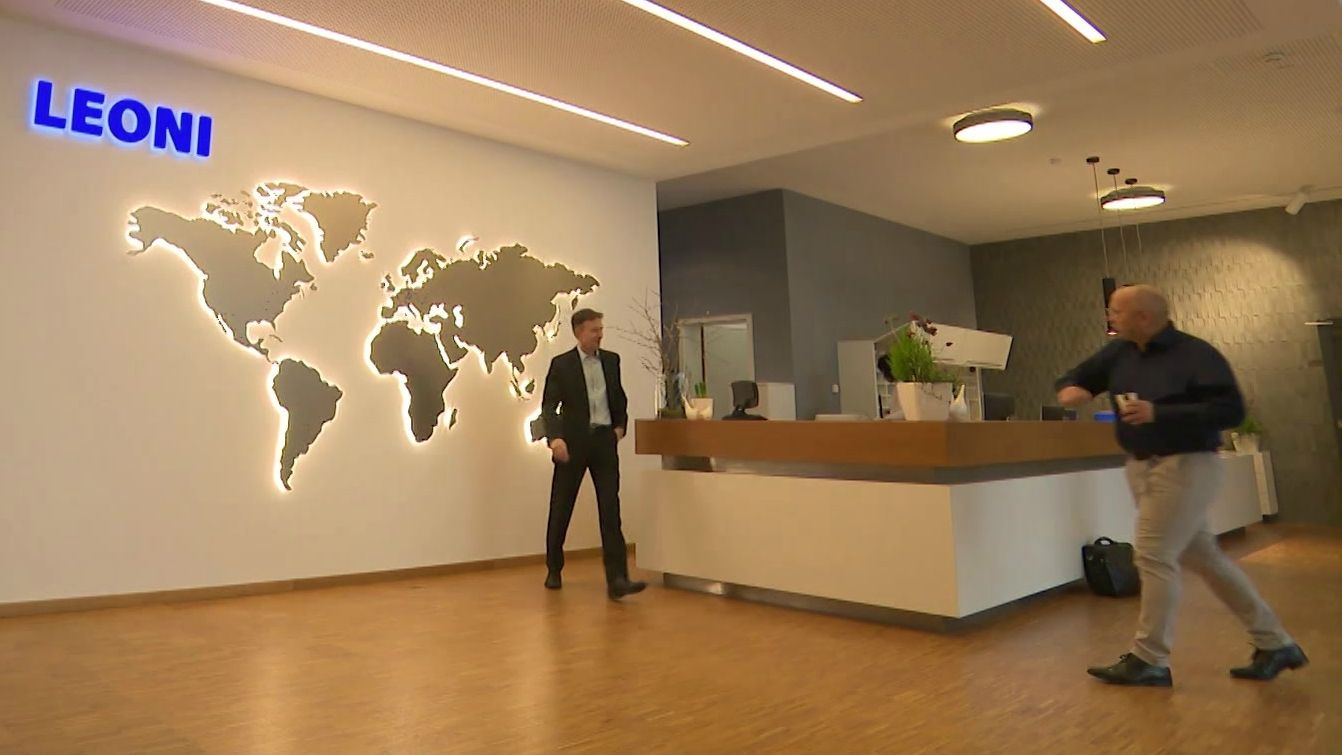 Eingangsbereich bei Leoni mit Anmeldetheke und leuchtender Weltkarte im Hintergrund