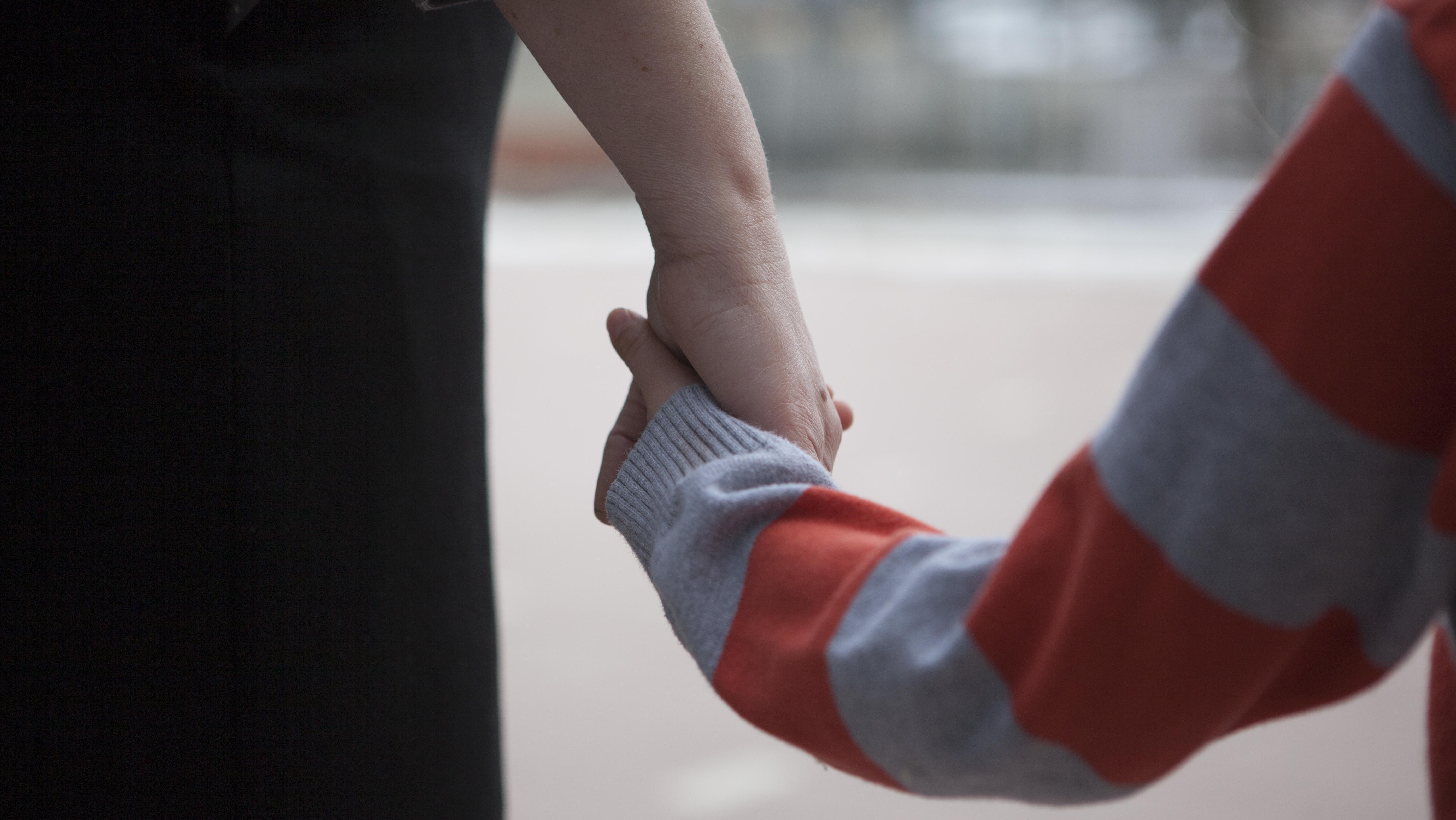 Symbolbild: Eine Frau hält ein Kind an der Hand