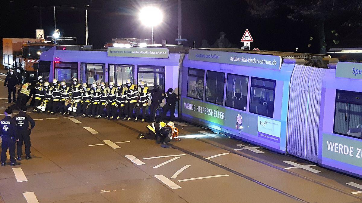 Mitarbeiter der Feuerwehr versuchen Straßenbahn wieder ins Gleis zu schieben