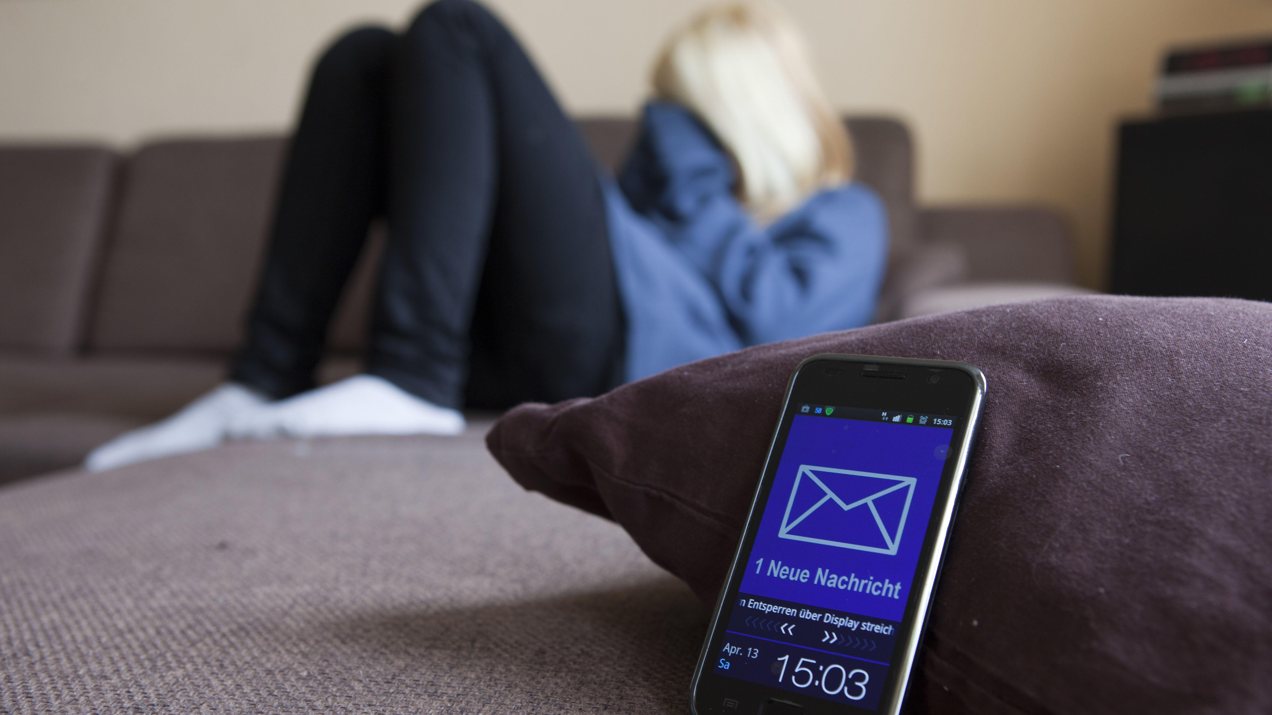 Symbolbild Cybermobbing:  Eine Jugendliche sitzt in einem Wohnzimmer und weint, weil sie per Mail von ihren Mitschülern gemobbt wird.