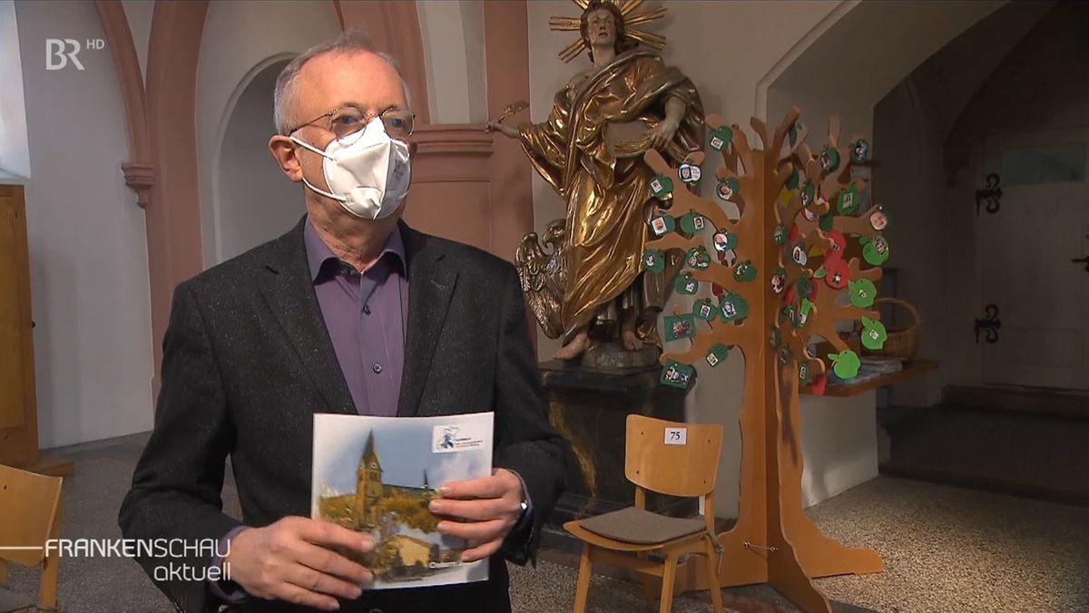 Ein Mann mit Maske steht in einer Kirche und hält einen Prospekt in der Hand.