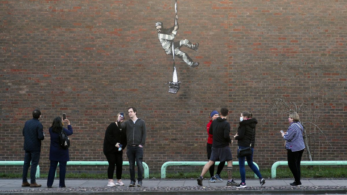 Kunstfans fotografieren sich vor dem Wandbild