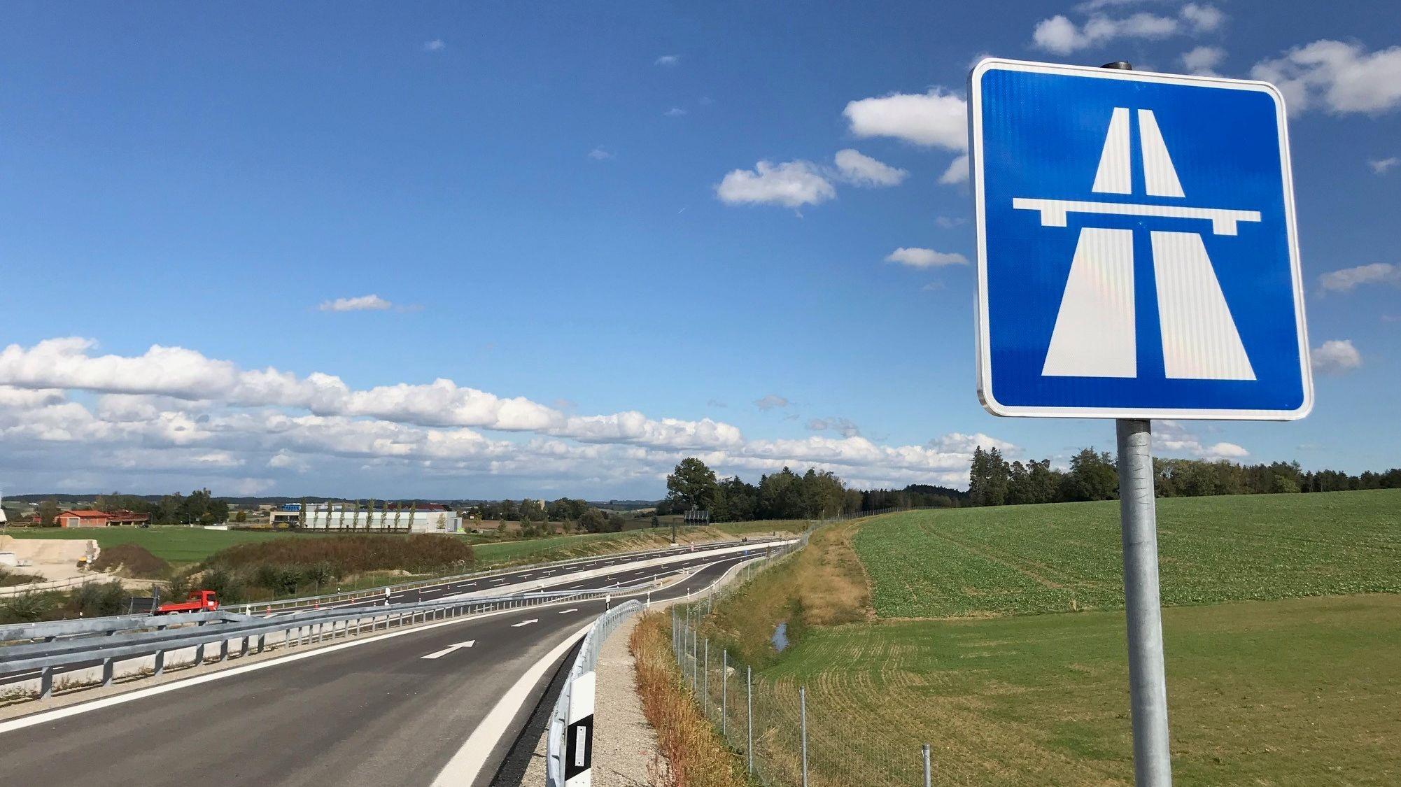 Die Fahrbahn der neu gebauten A94 zieht sich durchs Isental - im Vordergrund ein blaues Autobahn-Straßenschild