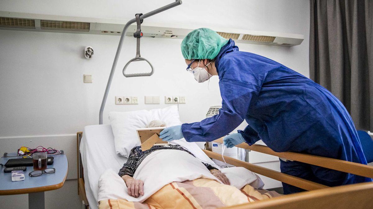 Eine Pflegekraft zeigt einem Koronapatienten ein Familienfoto