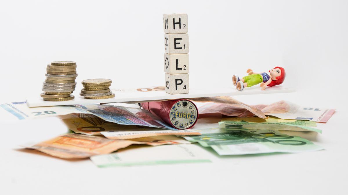 """Symbolbild Corona/Wirtschaft/Kredite: Euro-Scheine und Münzen, eine umgekippte Spielzeugfigur und vier Buchstabenwürfel mit dem Wort """"Help"""""""