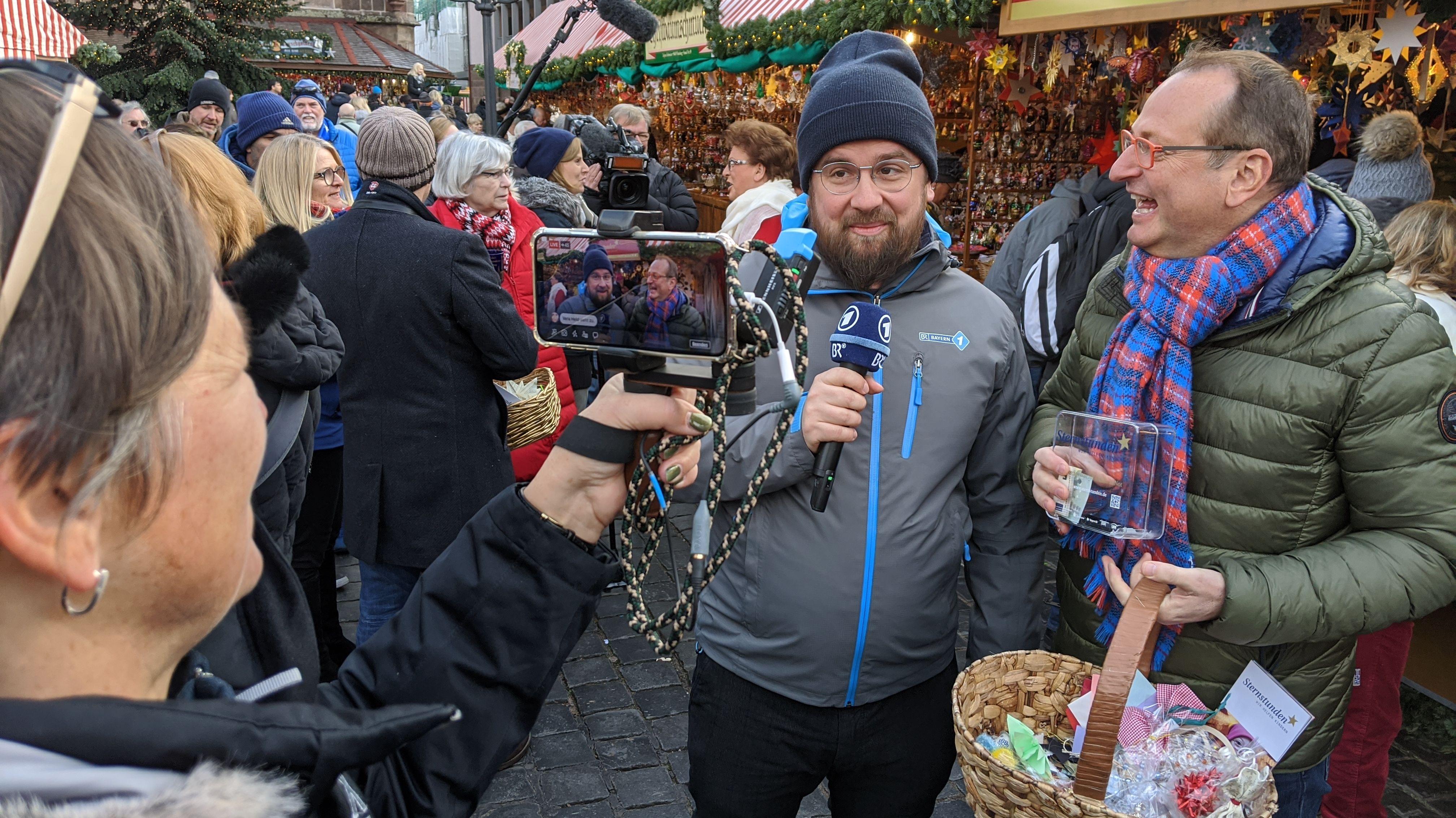 Matthias Rüd mit Mikrophon schaut in Handykamera, daneben steht der lachende Volker Heißmann