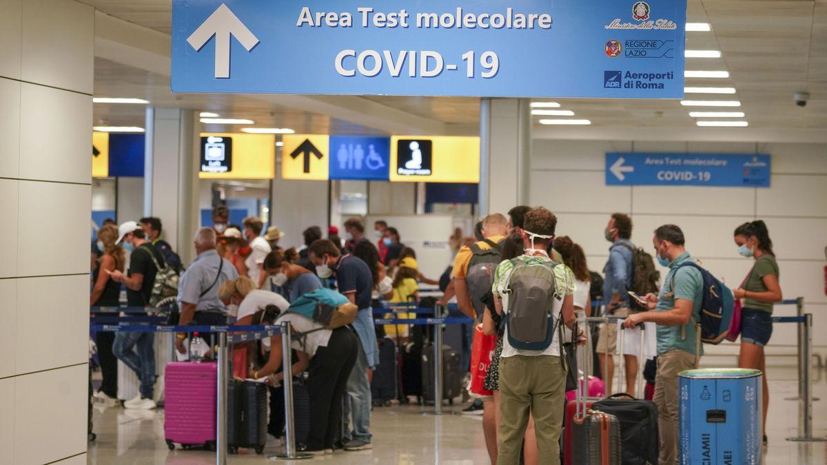 Urlauber stehen im Flughafen in einer Schlange für einen Covid-19-Test.