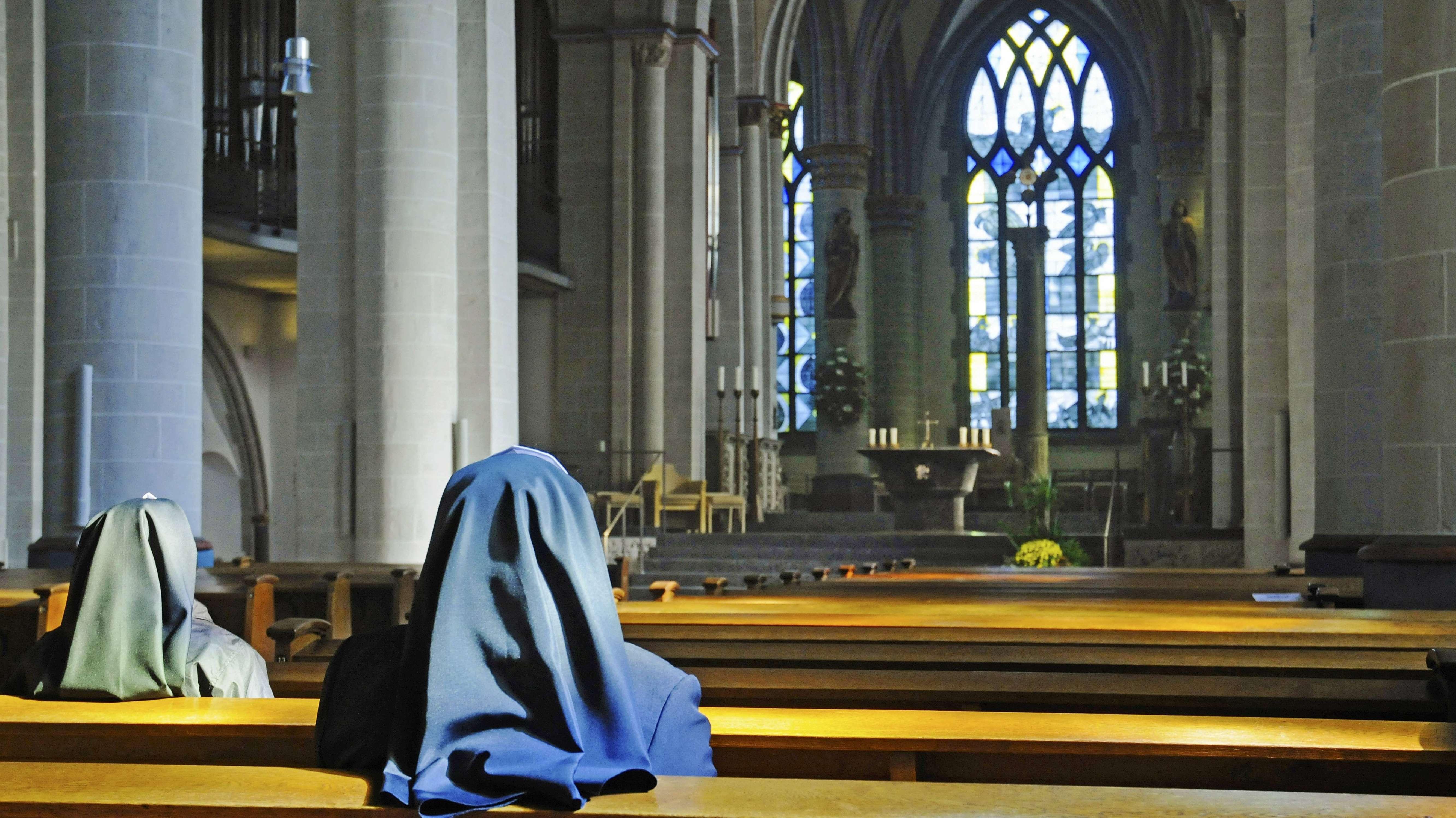 Rückansicht: Nonnen sitzen in einer Kirche und blicken auf den Altar