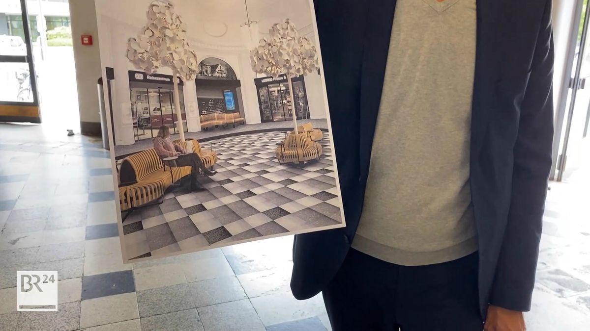 Ein Mann hält ein Bild hoch, wie der Bahnhof in Zukunft aussehen könnte.
