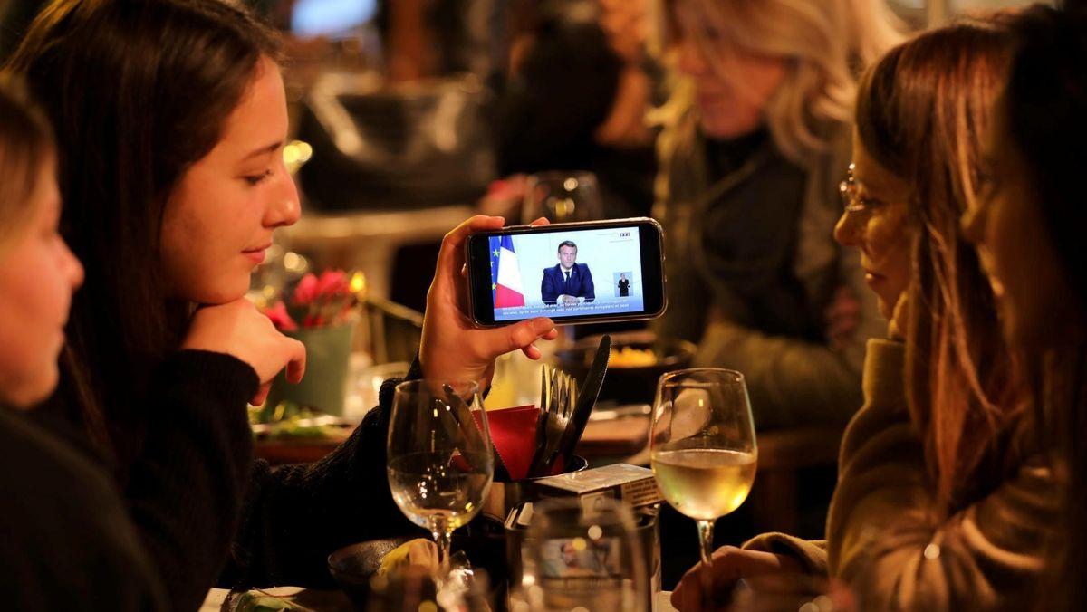 Eine Gruppe Französinnen sieht sich die Rede von Präsident Macron auf dem Handy an.