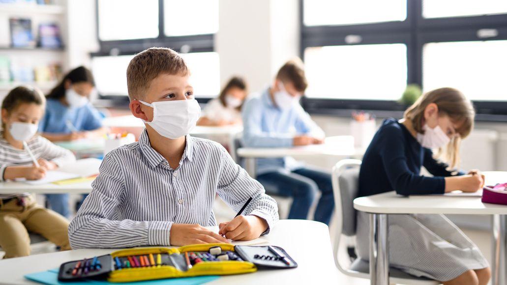 Kinder mit Maske im Klassenzimmer