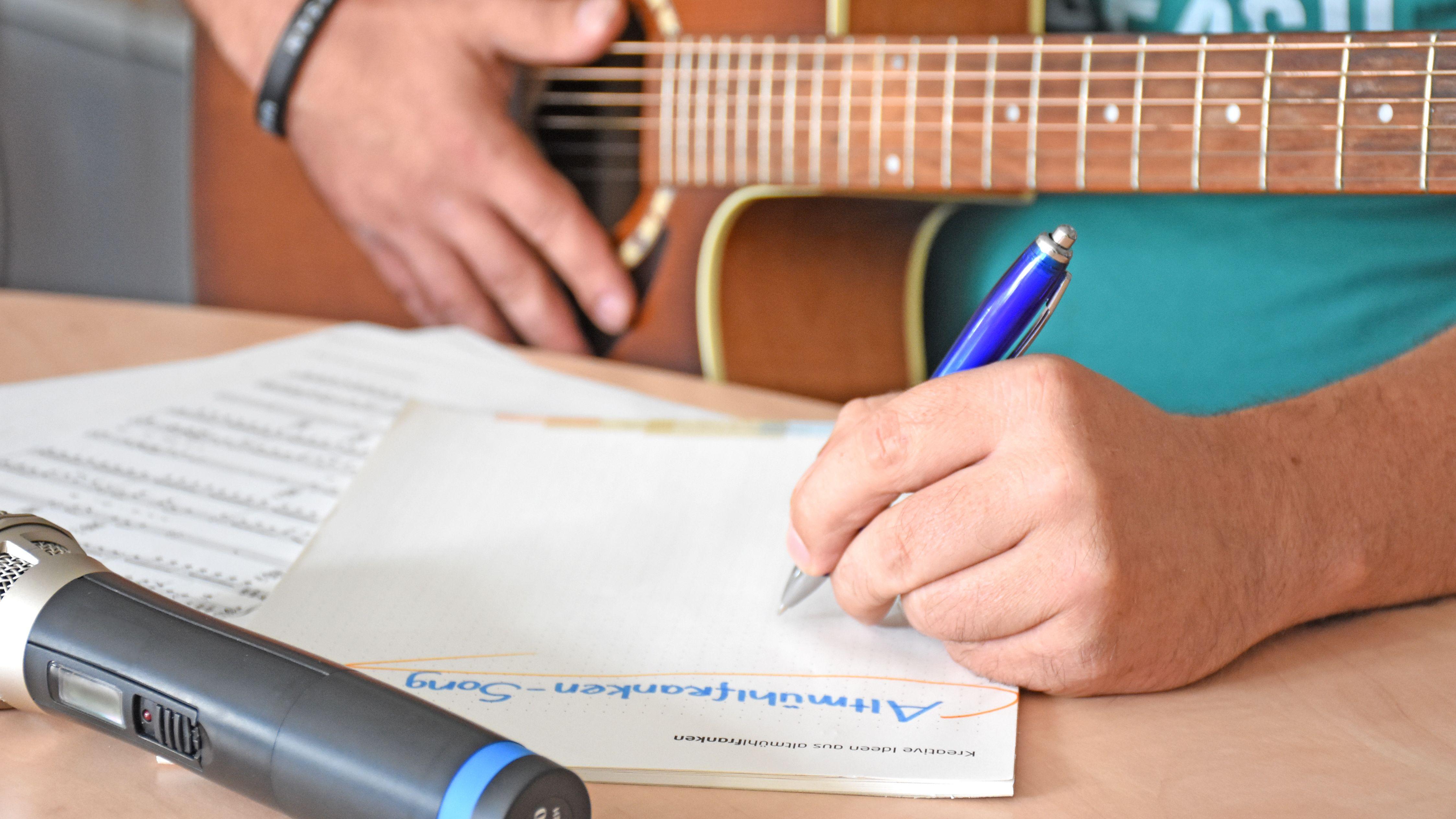 Songwriter notiert sich seine Liederideen, er hält eine Gitarre