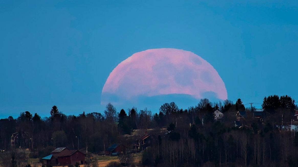 Vollmond am Horizont. Der Vergleich zu den Häusern, die acht Kilometer vom Fotografen entfernt sind, lässt den Mond in der Nähe des Horizonts größer wirken.