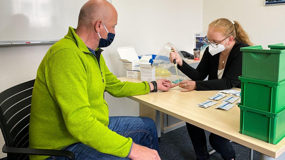 Eine Frau sticht Michael Herrmann in den Finger, um ihm Blut für einen Corona-Antikörper-Test abzunehmen.